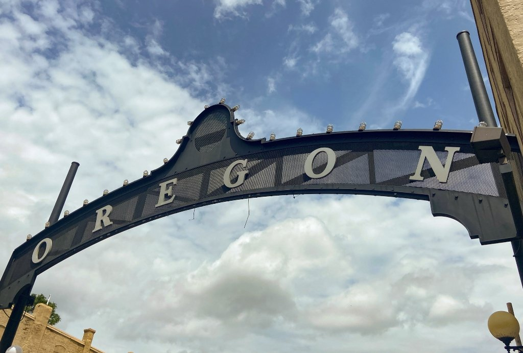 A black iron arch that says Oregon lets visitors know they've entered this historic district in Dayton.
