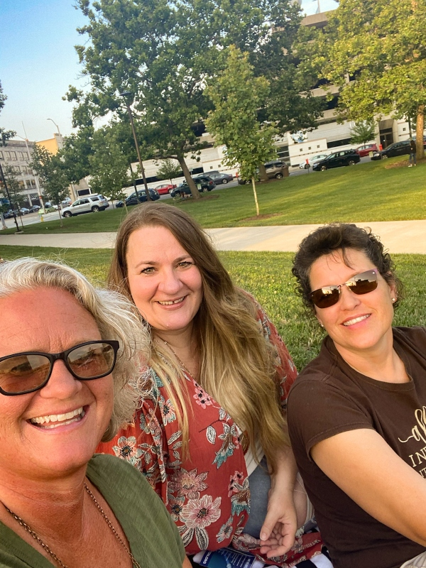 Three women laughing at an outdoor park.