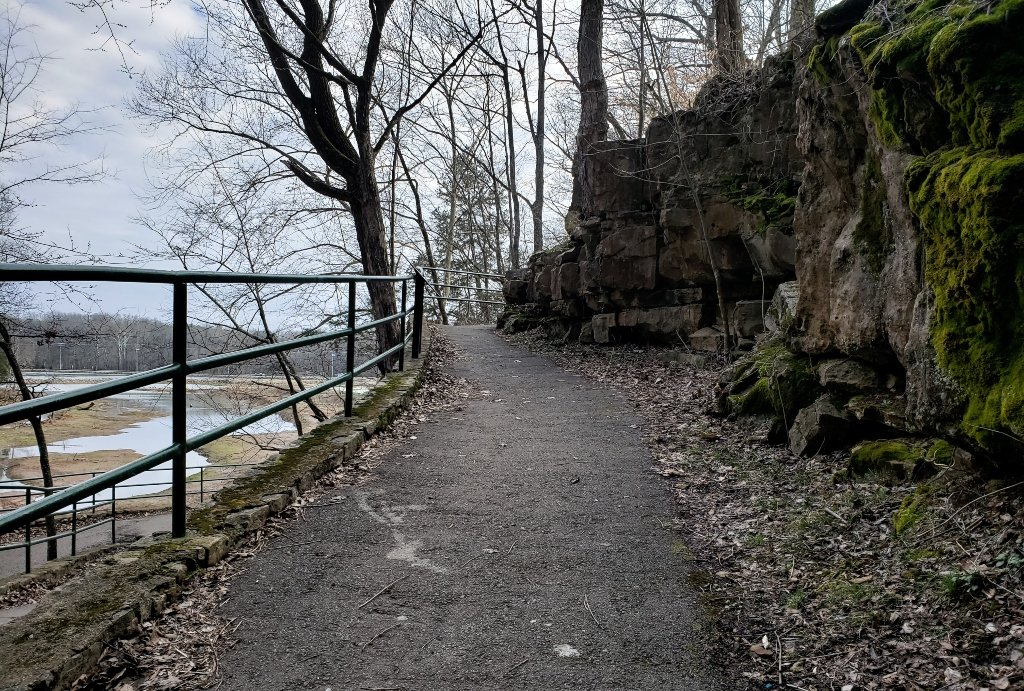 A paved trail goes uphill with a railing on one side with views of the marsh and a rock wall on the other at Dunbar Cave State Park.