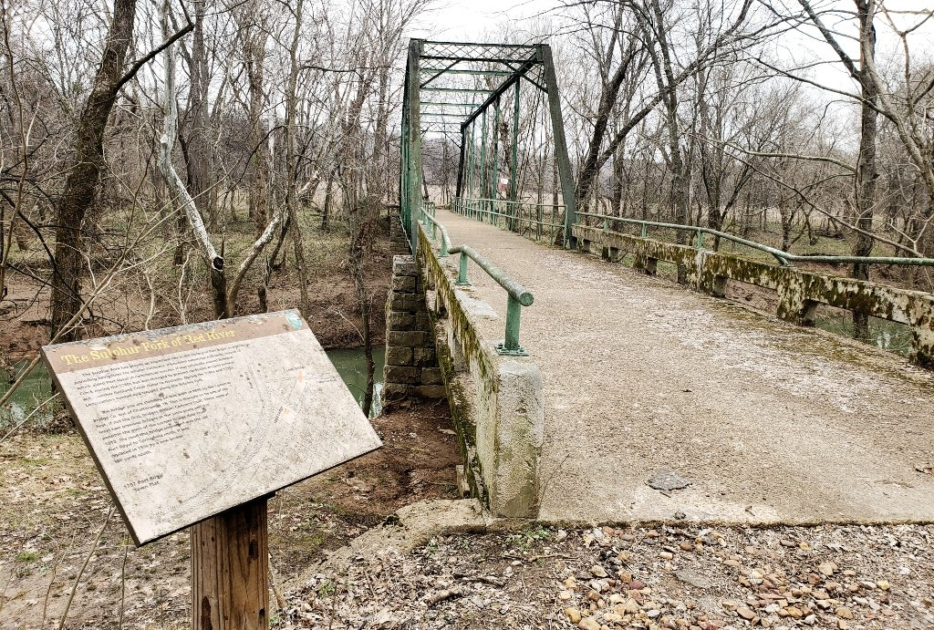 An historic iron bridge crossing the river near a placard with more information.