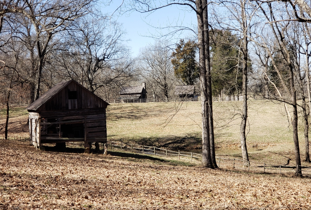 A wooded setting with a log cabin in the foreground and two other log cabins in the distance.
