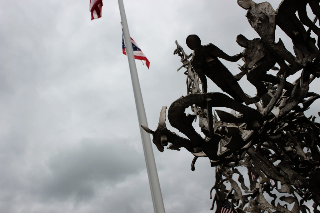 An Ohio and U.S. Flag fly on a stormy sky with figures of metal cut outs nearby.