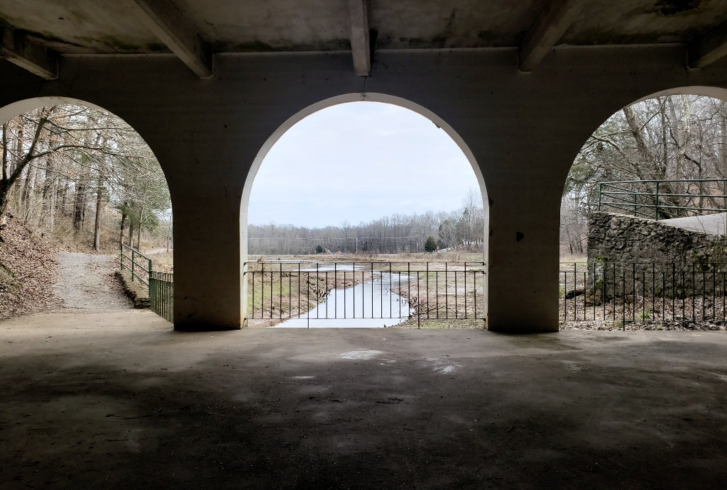 Lookiing through arched doorways at the stream that runs through Dunbar Cave State Park.