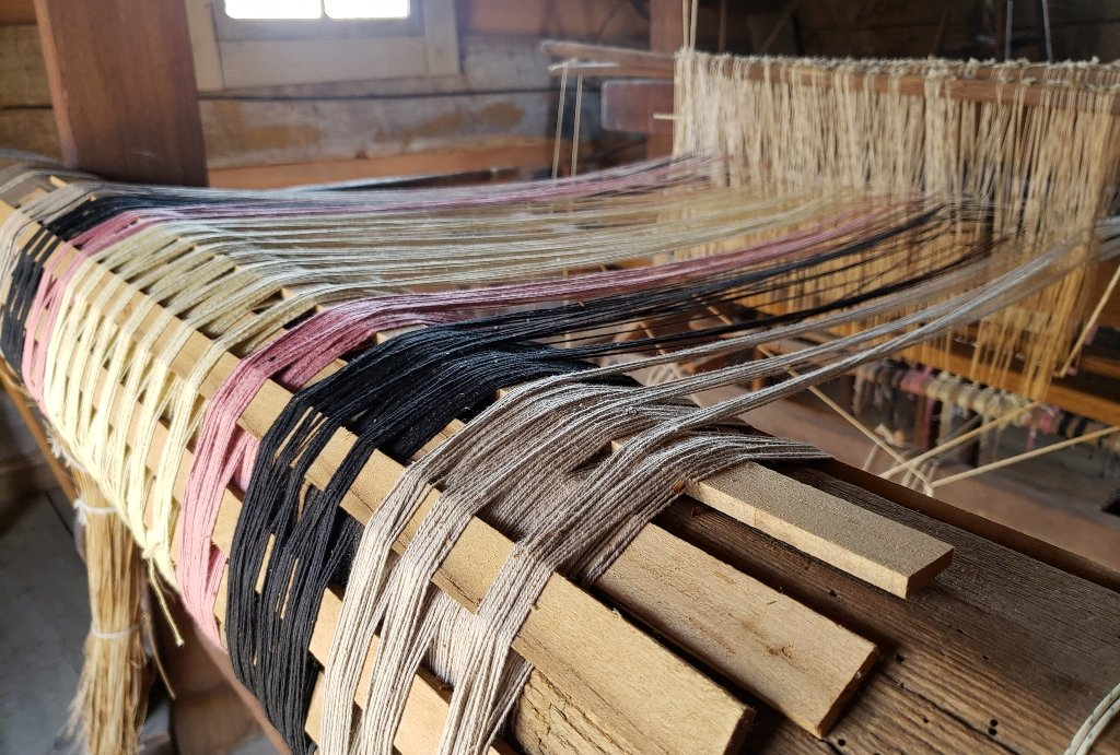 Threads are being woven together on a wooden machine.