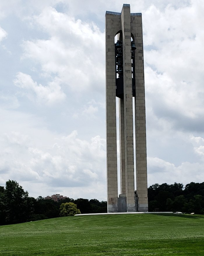 The carillon bell tower standing on a grassy knoll with blue skies behind it.