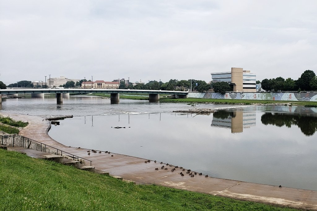 The Great Miami Riverway as it flows through Dayton. Buildings are reflected in the water, ducks are resting along the bank, a bridge crosses the water.