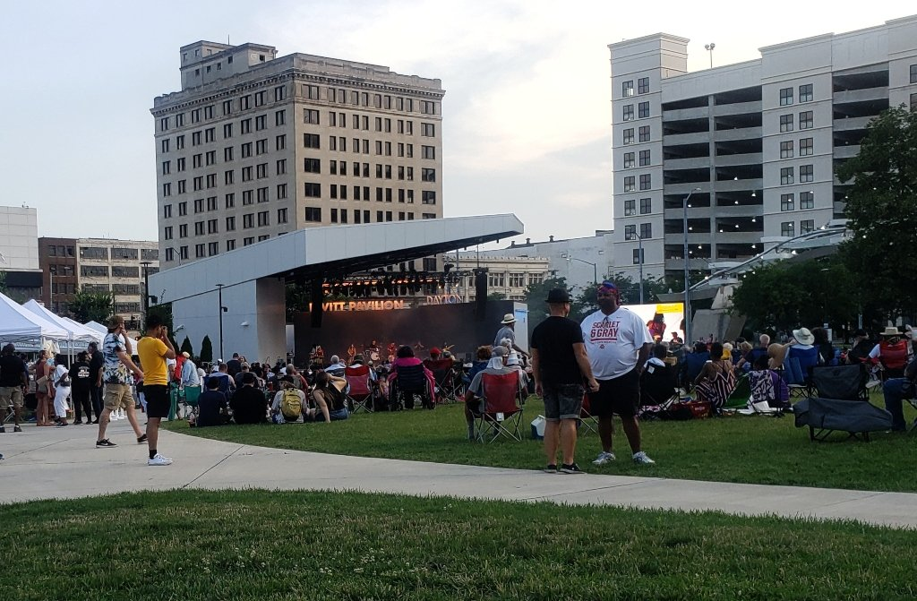 Leavitt Pavilion is a popular spot for free summer concerts in Dayton. This image shows the concert stage behind people walking around, standing and seated listening to the band or talking.